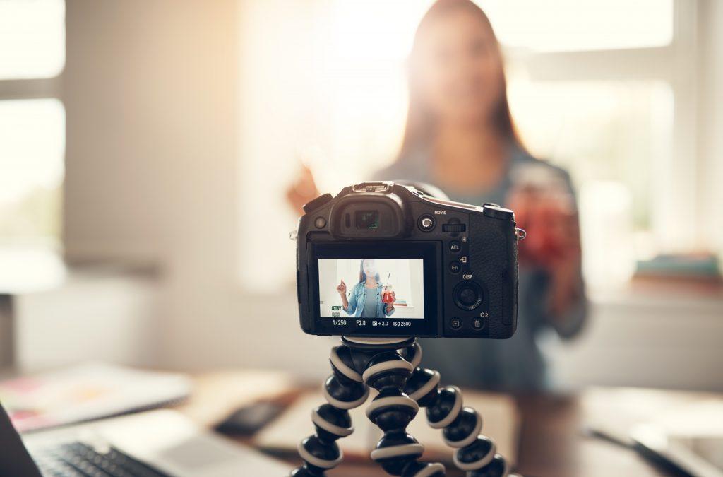 Chica grabandose un curso online, se ve la cámara y ella en el fondo