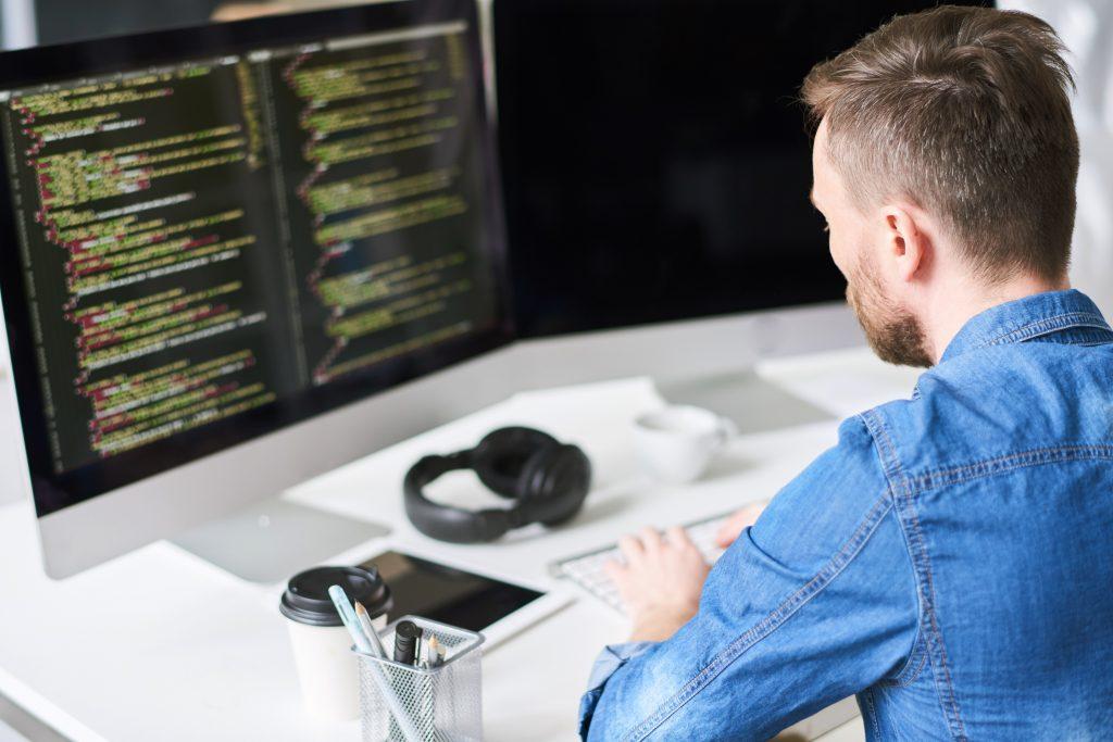 Programador sentado de espaldas mientras escribe el código de una aplicación
