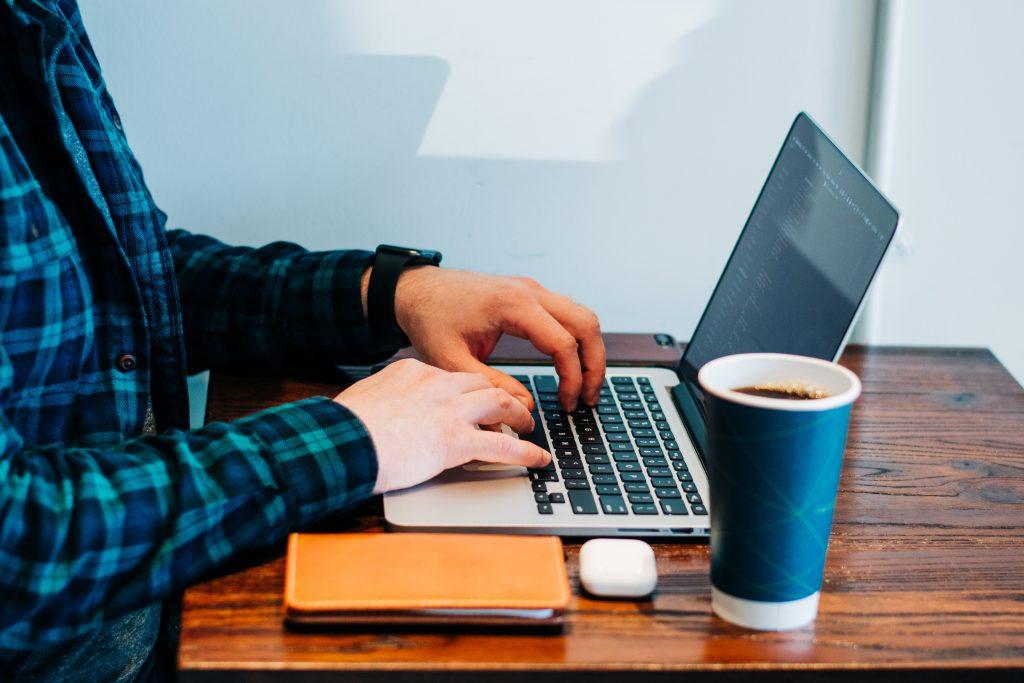 Persona sentada en un escritorio de madera escribiendo en un laptop