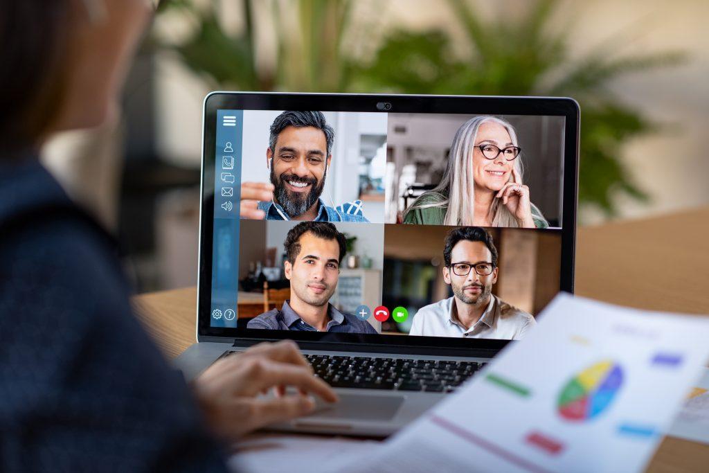 Una persona vista desde detrás haciendo una videoconferencia con cuatro alumnos.